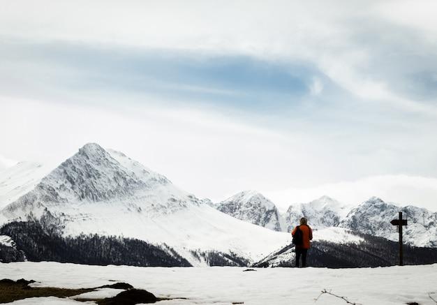 木の看板の隣でトレッキングをしている男。丘の中の雪。冬のハイキング。アストゥリアス