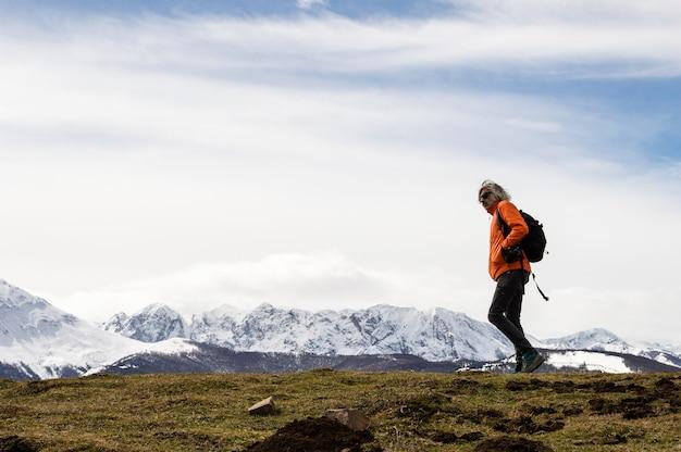 Человек делает треккинг рядом с деревянным указателем. снег в горах. зимний поход. астурия