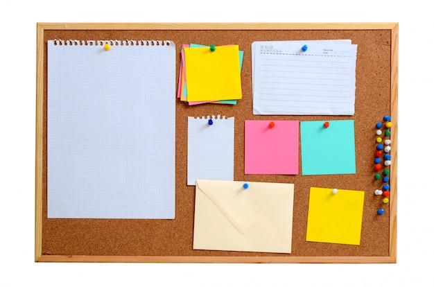 空のノートが茶色のコルクボードに固定されています