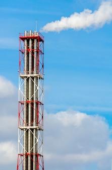 青い空を背景に喫煙工場のパイプ