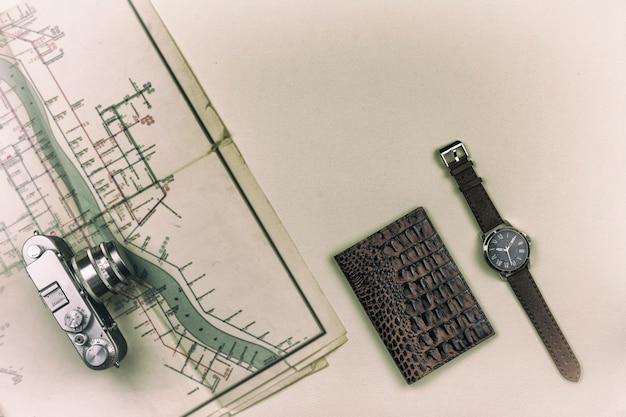 レトロなカメラは古い地図です。腕時計付きのパスポートがテーブルの上にあります。夏の旅