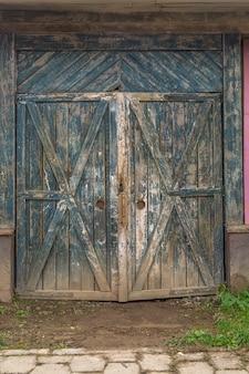 倉庫に大きな木製の緑のゲート。工業地区の古い倉庫。