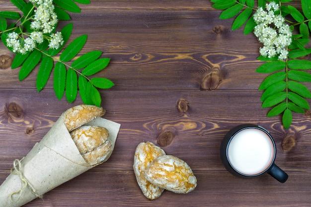平置き。テーブルの上に、春の花、ミルクのマグカップと甘い自家製クッキー。