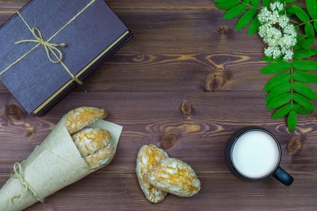 平置き。テーブルの上に、春の花、牛乳と甘い自家製クッキーや本のマグカップ。