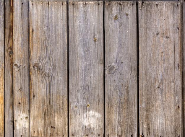 家の古い未塗装の壁。古い木の塀。