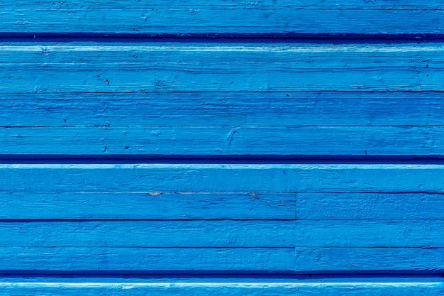 テクスチャ家の古い塗られた壁。古い木の塀。青いペンキ。