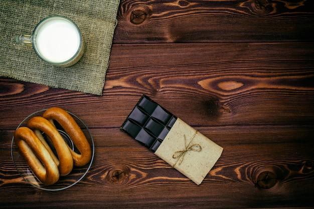 平置き。ミルクのカップベーグルとテーブルの上のダークチョコレート