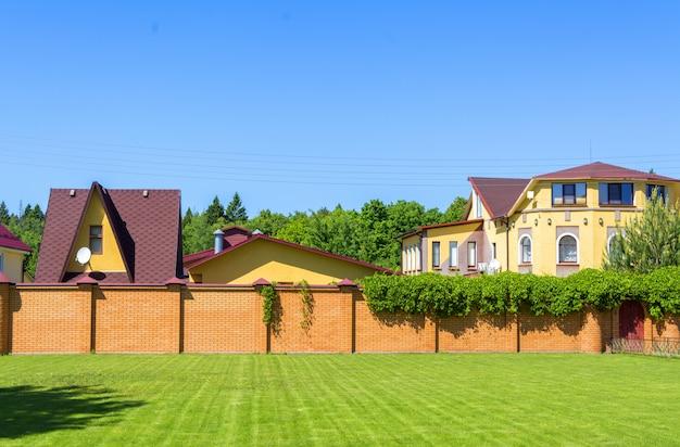 レンガの塀の後ろにガレージ付きの美しいカントリーハウス。