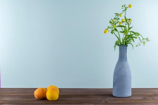 アプリコットは木製のテーブルに置かれています。青い背景に野生の花瓶と花瓶。夏の気分