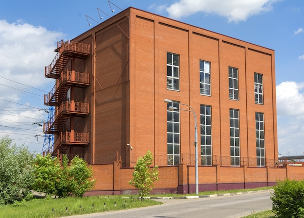 Здание небольшой фабрики из красного кирпича.