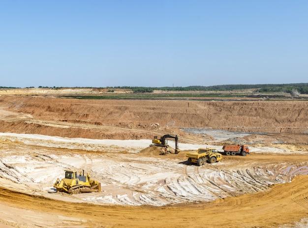 掘削機はダンプトラックに砂を積み込みます。採石場での砂の採掘