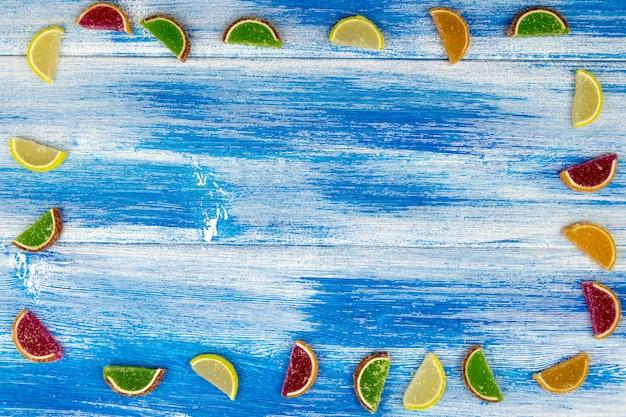 柑橘類のスライスの形のマルチカラーマーマレードは、青のボード上のフレームとしてレイアウト