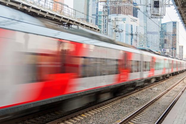 Скоростной поезд курсирует по городу на фоне небоскребов.