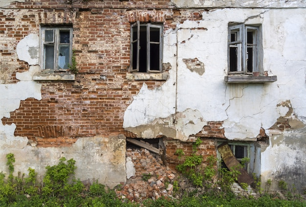 修理が必要な、窓のある古い家の壁