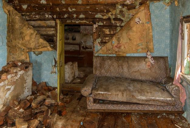 放棄された農家部屋のソファー。破滅と汚れ