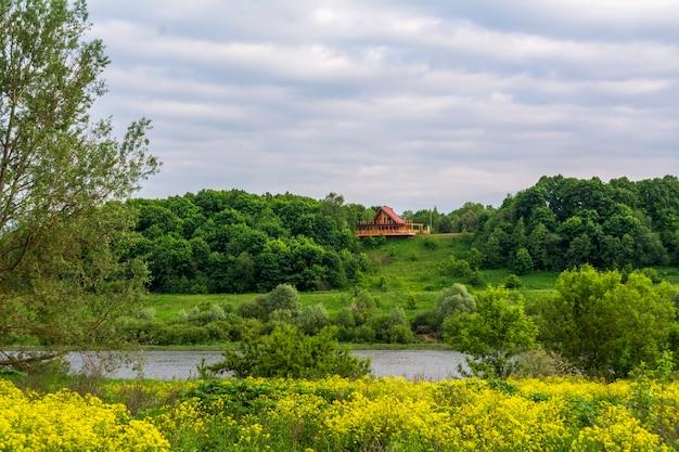 家は川の上に位置しています。花の前景の川の谷で