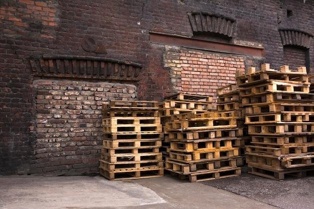 木製パレットは古い倉庫の庭に積み上げられています。