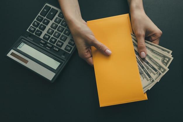 女の子は暗闇の中でお金で黄色い封筒を持っています。