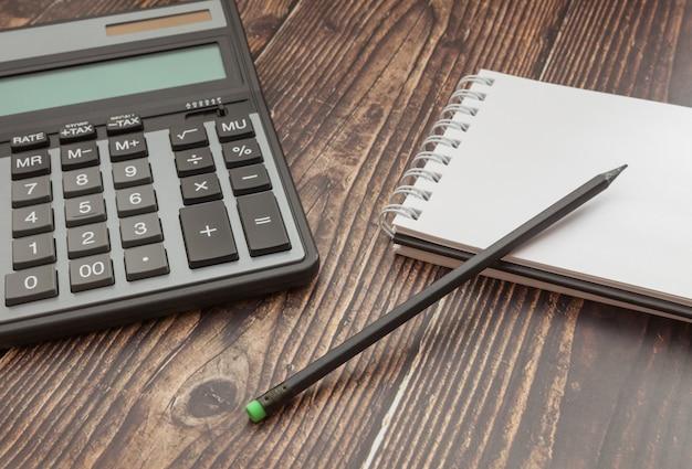 ノートブックと木製のテーブル上の電卓