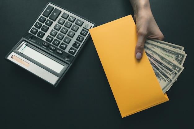 黒革の机の上に電卓、女の子は彼女の手にお金と黄色の封筒を保持しています