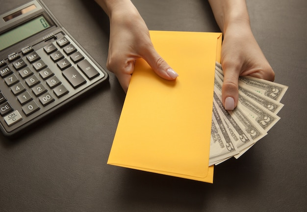 封筒に給料を受け取るの概念。暗いテーブルの上のお金で黄色い封筒。