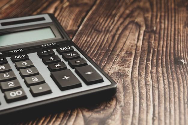 Современный калькулятор на деревянном столе, концепция дела