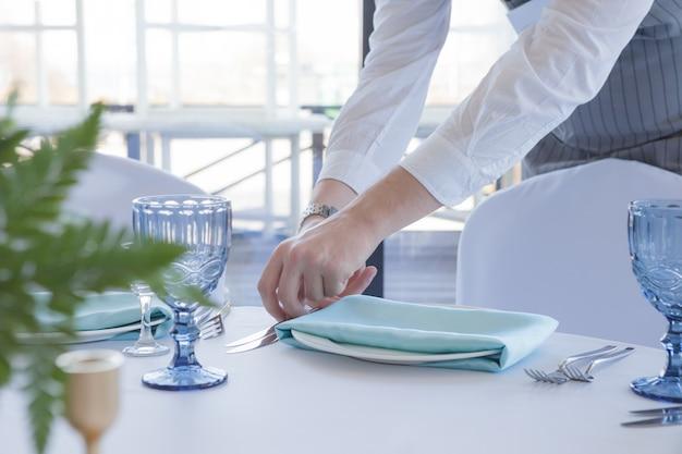 レストランのウェイターは、結婚式のお祝いのためのテーブルを提供しています