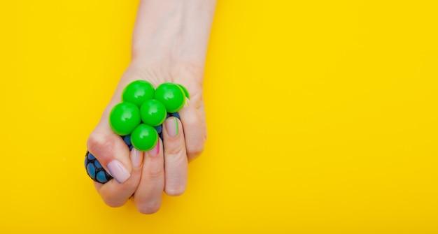 Антистрессовая игрушка в женской руке на желтом