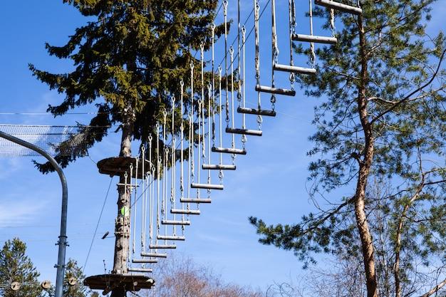 夏の森の風光明媚な青い空の風景のロープアドベンチャーパーク。障害を克服し、高さに達する。