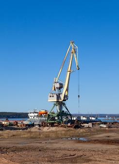 晴れた夏の日にパレットを積み降ろしするための機械とフォークリフトの港のクレーン