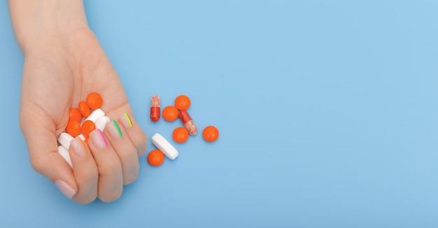 Женские руки с красивым современным маникюром и таблетками