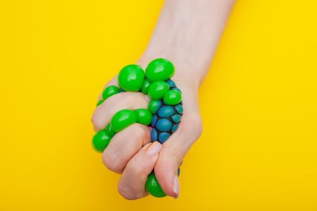 Крупный план. антистрессовая игрушка в женской руке на желтом
