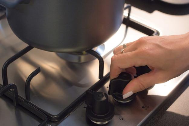 キッチンガスストーブから燃やすガスを開く手の女性。