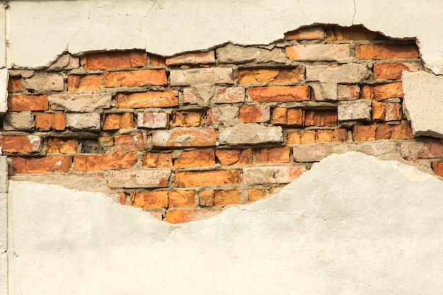 部分的に破壊された石膏、背景またはテクスチャを有するレンガ壁