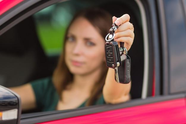 車の中のキーを持つ美しい少女、新しい車を買う概念