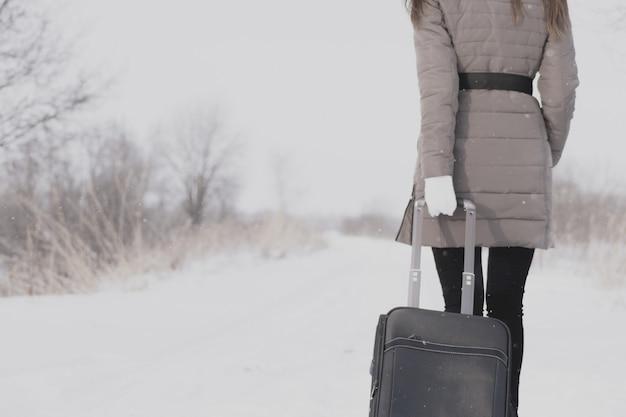 女の子はスーツケースで旅行しています。冬の道と若い女の子。