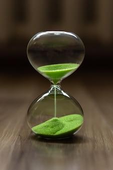 ぼんやりとした背景に緑の砂の砂時計