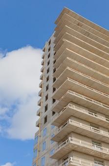 青い空を背景に新しい多階建ての建物(超高層ビル)のコンクリート構造