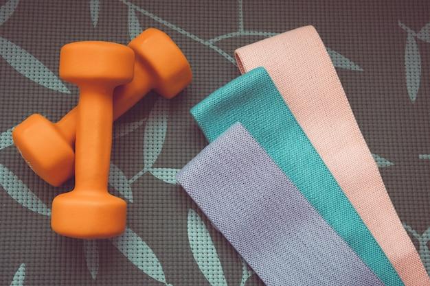Оранжевая гантель для фитнеса и спортивных резинок на сером фоне, концепция домашних тренировок