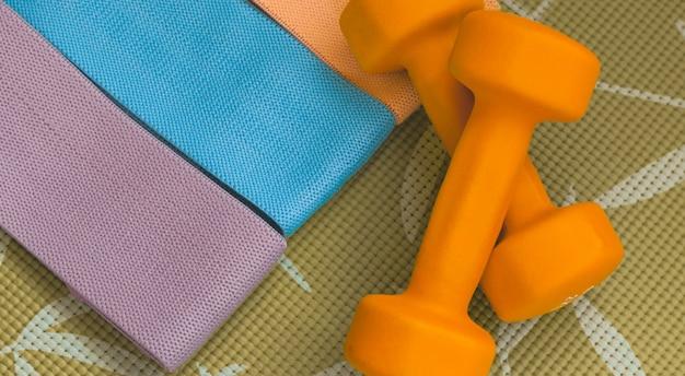 Оранжевые гантели на зеленом спортивном ковре и три эластичные резинки для ног. вид сверху.