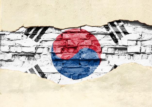Национальный флаг южной кореи на фоне кирпича. кирпичная стена с частично разрушенной штукатуркой, фона или текстуры.