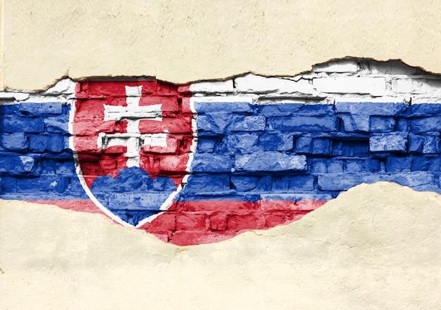 Национальный флаг словакии на фоне кирпича. кирпичная стена с частично разрушенной штукатуркой, фона или текстуры.