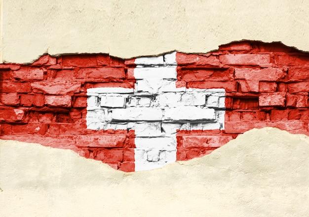 Национальный флаг швейцарии на фоне кирпича. кирпичная стена с частично разрушенной штукатуркой, фона или текстуры.