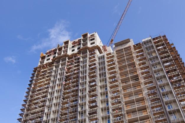 Строительный кран, строительство нового небоскреба или многоквартирного дома