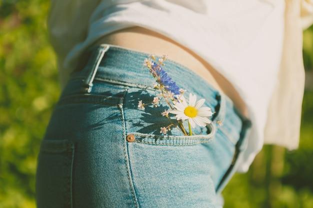 Крупный план. девушка в синих джинсах с цветами в кармане на фоне природы.
