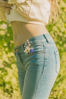 Красивая девушка в синих джинсах с ромашкой в кармане. прогулка в зеленом парке.