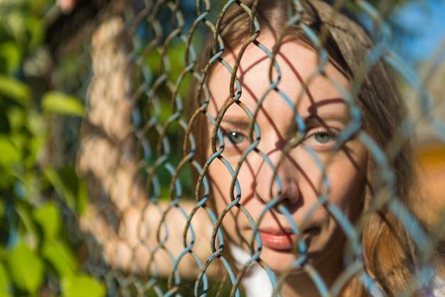 Девушка в парке смотрит через металлический забор.