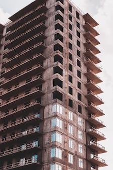 空を背景にコンクリートと金属で作られた建設中の建物