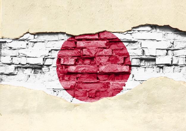 Национальный флаг японии на фоне кирпича. кирпичная стена с частично разрушенной штукатуркой.