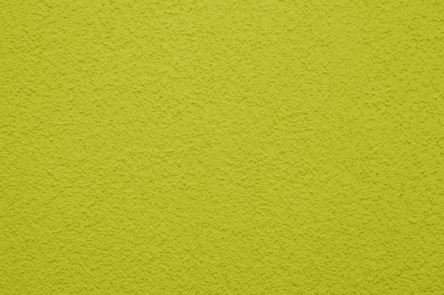 Красочная текстура бетонной стены, покрашенный цвет предпосылки желтый.